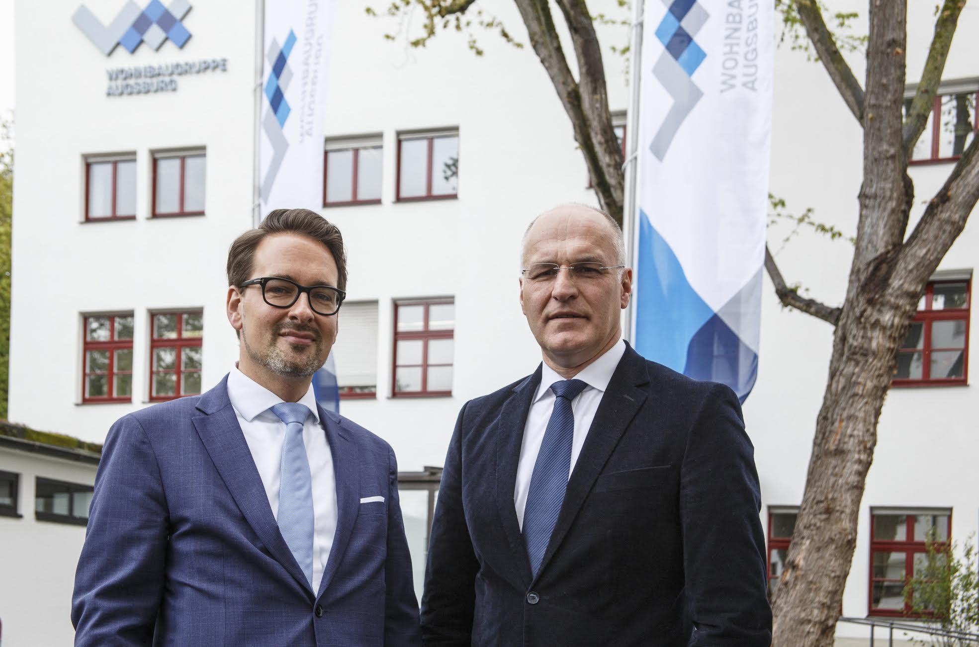 Mit neuem Logo im Hintergrund: Dr. Mark Dominik Hoppe (li.), und Oberbürgermeister Dr. Kurt Gribl vor der Geschäftsstelle der Wohnbaugruppe Augsburg.